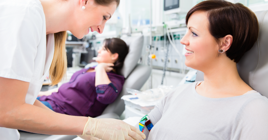 Woman smiling while donating blood and speaking to nurse