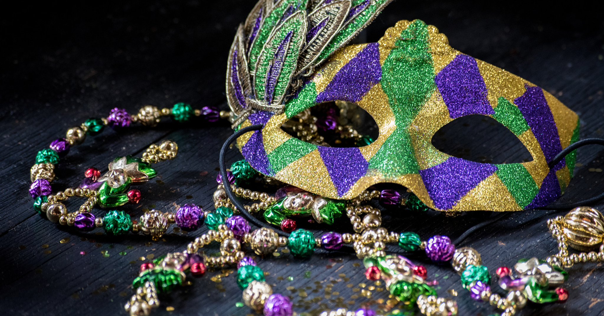 Mardi Gras mask and beads lying on a table