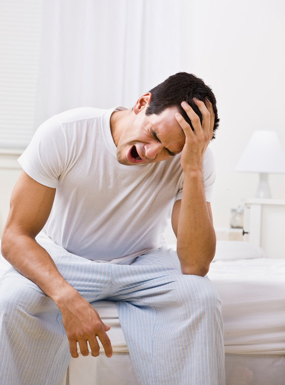 A man yawning. He is sitting on the edge of a bed. Vertically framed shot.