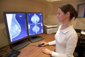 Radiology technician examines mammography test on location