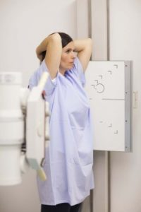 Woman placing her arms on her head while standing in front of a machine in an examination room